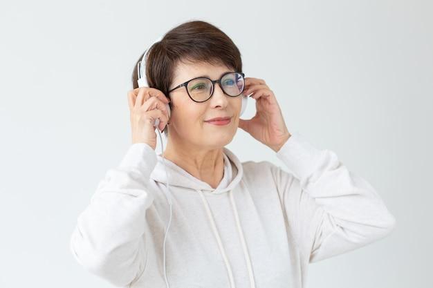 セーターとメガネのかわいいポジティブな中年女性は、白い壁に立っているワイヤーヘッドホンで音楽を聴いています。趣味のコンセプトとお気に入りのラジオ局への加入。