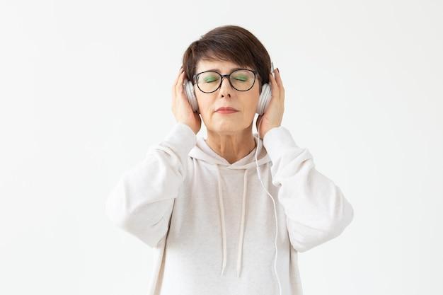 セーターとメガネでかわいいポジティブ中年女性がワイヤーヘッドホンで音楽を聴いています
