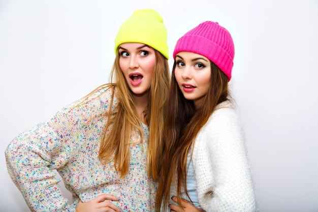 Carino ritratto positivo della migliore amica belle giovani donne, inverno, cappelli al neon, maglioni accoglienti, abbracci e divertimento, trucco luminoso naturale, due sorelle sorridenti, gioia, coppia, emozioni, muro bianco.