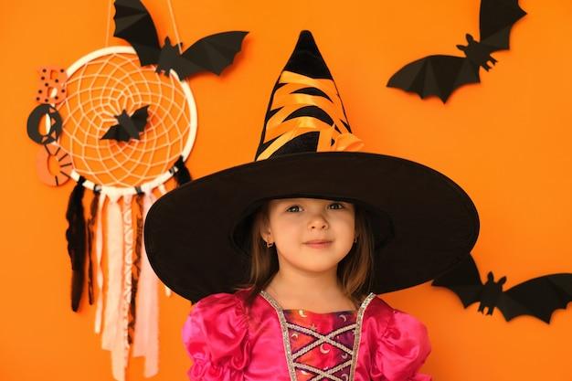 ハロウィーンの装飾とオレンジ色のスタジオの背景にかわいいポジティブな笑顔の少女