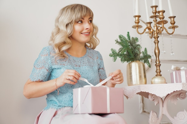 Cute positive woman near christmas tree opening gift in pink box