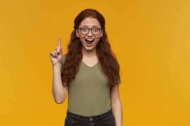 Милая, позитивная женщина с длинными рыжими волосами. в зеленой футболке и очках. концепция людей и эмоций. поднимает указательный палец вверх, в голову пришла идея. изолированные над оранжевой стеной