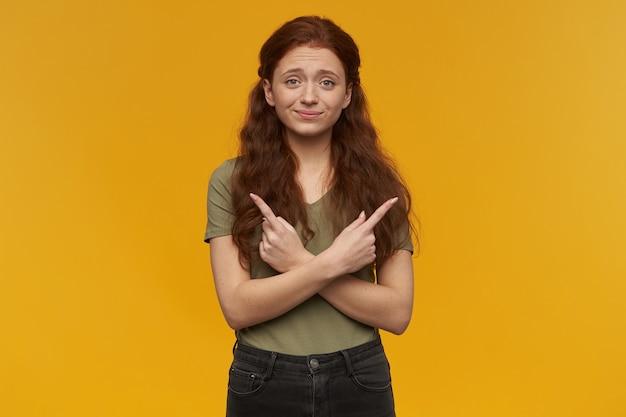 긴 생강 머리를 가진 귀엽고 긍정적 인 여성. 녹색 티셔츠를 입고. 사람과 감정 개념. 복사 공간에서 불확실하게 양쪽을 가리 킵니다. 오렌지 벽 위에 절연