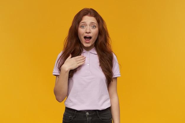 긴 생강 머리를 가진 귀엽고 긍정적 인 여성. 분홍색 티셔츠를 입고. 사람과 감정 개념. 자신을 가리키고 있습니다. 자신을 소개합니다. 오렌지 벽 위에 절연
