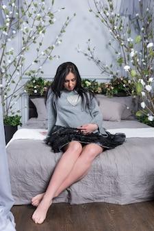 ベッドルームのベッドステッドに花と一緒にベッドに座っている間、腹に手を保つドレスを着たかわいい妊娠中のブルネットの女性。妊娠の最後の数ヶ月。