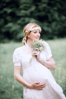 野生の花の花束を持つかわいい妊婦