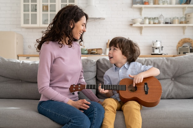 Cute preschool boy hold ukulele laugh sitting together with mom in living room family leisure time