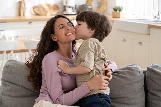 귀여운 취학 전 소년이 키스를 하고 기쁨에서 눈을 감고 행복한 미소를 짓고 있는 젊은 어머니를 껴안습니다.