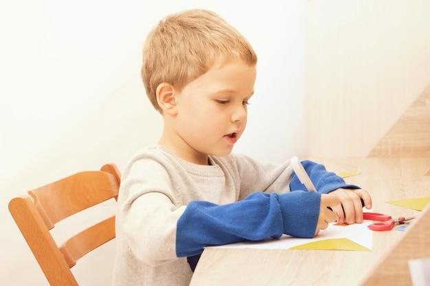 Милый дошкольник сидит за столом и делает аппликацию из цветного картона. концепция домашнего образования или развивающие мероприятия. онлайн-обучение.