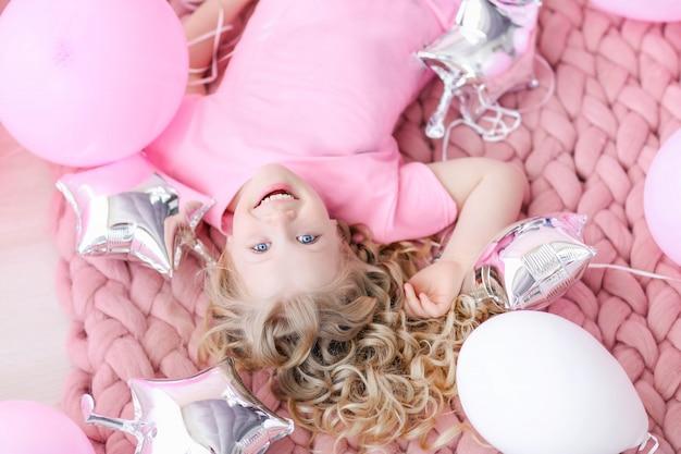 분홍색 옷과 분홍색 방에 귀여운 유치원 아이.