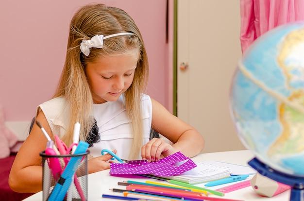 Cute preschool girl is doing her creative homework.
