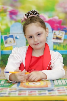 A cute preschool girl is sitting at a school desk holding a pen and looking at the camera.