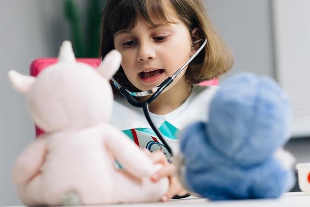 귀여운 유치원 여자 아이, 의료 유니폼을 입고 애완 동물 호흡, 앵무새 및 장난감 환자 듣기