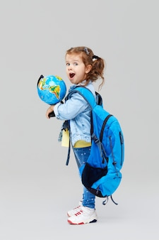 Cute preschool girl with a blue backpack on her back, holding a globe in her hands.