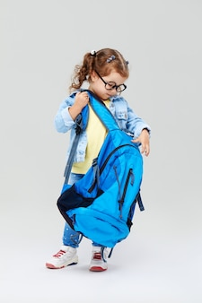 Cute preschool girl with a blue backpack on her back, holding a globe in her hands