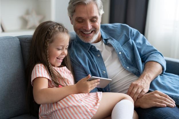 귀여운 미취학 아동은 아버지가 스마트폰으로 뭔가를 보여주도록 도와주고, 똑똑한 작은 딸과 아빠는 소파에 앉아 휴대폰을 들고 있습니다
