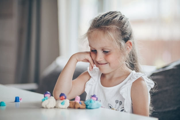 Cute preschooler girl playing educational games with plasticine figures preparing for school in kindergarten