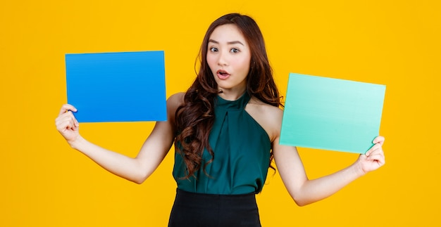 Cute and pretty curly hair asian female brunette holding green and blue blank board poses to camera with a joyful for advertising use purpose, studio shot isolated on yellow background.