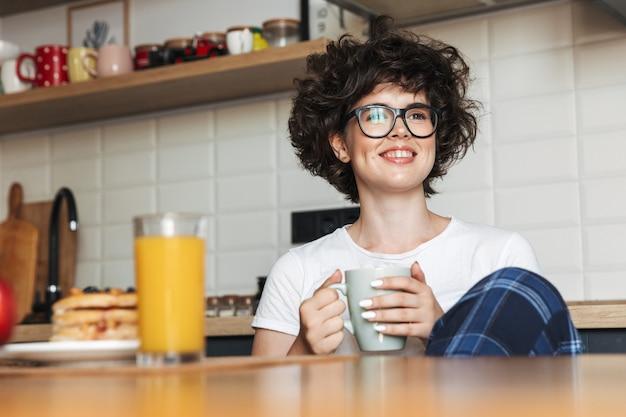 お茶を飲みながらキッチンに座っているかわいいかわいい巻き毛の女性