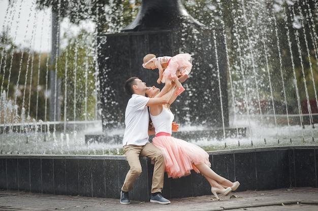 噴水の近くの公園を歩いているかわいいかわいい家族。一緒に家族を愛する。小さな赤ちゃんを持つ母と父。