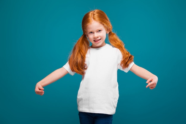 Cute, pretty, little girl in tee shirt with long red hair
