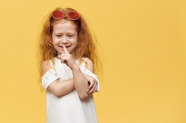 Cute pretty playful little girl with stylish sunglasses on her head holding index finger at her mouth, making silence gesture
