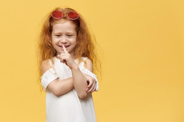 Bambina carina abbastanza giocosa con occhiali da sole alla moda sulla sua testa tenendo il dito indice alla bocca, facendo gesto di silenzio