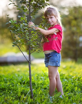 Cute pretty smiling child girl with gray eyes and long blond hair in summer clothing holding to young green sapling tree on blurred sunny park or garden