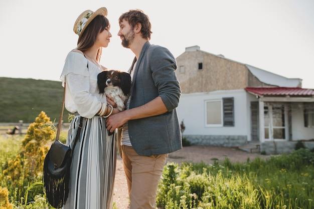 Симпатичная довольно стильная хипстерская влюбленная пара, гуляющая с собакой в сельской местности, летняя мода в стиле бохо, романтика