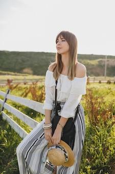 Симпатичный довольно солнечный портрет улыбающейся молодой красивой стильной женщины, весенне-летняя модная тенденция, стиль бохо, соломенная шляпа, загородные выходные, солнечный, черный кошелек