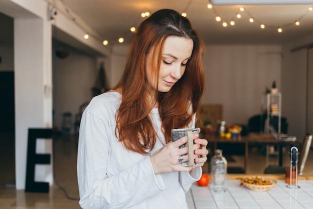 Ritratto di adolescente carino e grazioso che beve caffè
