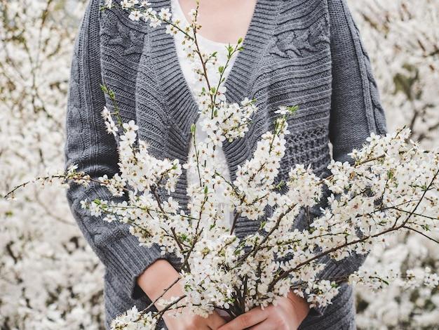 꽃 피는 나무의 배경에 귀엽고 예쁜 여자. 휴식과 휴식의 개념