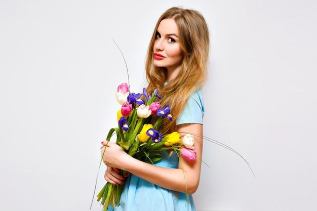 Donna graziosa sveglia che posa con bouquet di primavera pastello tenero, muro bianco, vacanza presente, abito vintage, lunghi capelli biondi e trucco naturale.