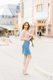 Cute pretty woman with professional makeup in a pink top and denim skirt in a summer city holding a bouquet of white and pink roses