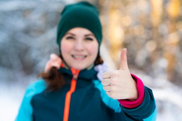 Милая довольно молодая счастливая женщина стоит на открытом воздухе в зимний холодный солнечный день в снежном парке или