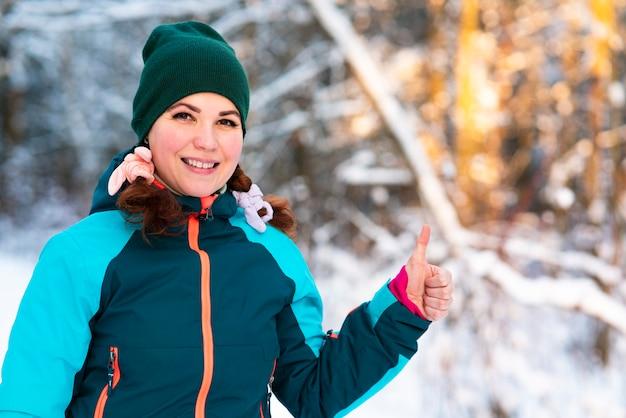 Милая довольно молодая счастливая женщина стоит на открытом воздухе в зимний холодный солнечный день в заснеженном парке