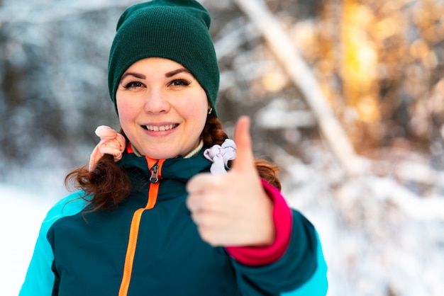 Cute pretty young happy woman is standing outdoors at winter cold sunny day in a snowy park or forest