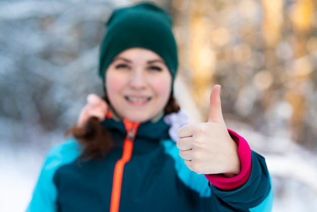 Cute pretty young happy woman is standing outdoors at winter cold sunny day in a snowy park or