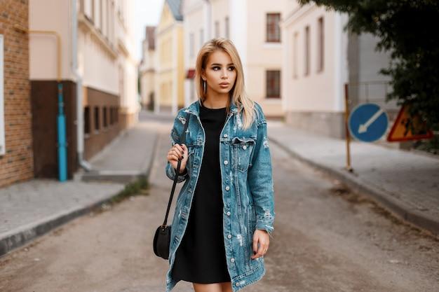빈티지 건물 근처 거리에 도시에서 포즈를 취하는 유행 긴 데님 재킷에 유행 핸드백과 검은 세련된 드레스에 귀여운 예쁜 젊은 여자