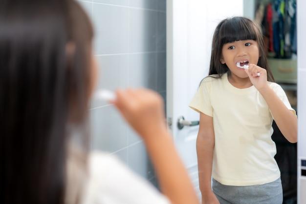 Милая девочка начальной школы чистит зубы и смотрит в зеркало в ванной комнате дома.