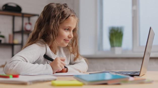 ノートパソコンを使用して自宅で勉強しているかわいい小学生の女の子。女子高生はオンラインレッスン、練習帳への書き込み、宿題をしています。