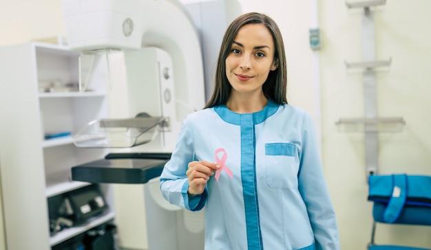 귀여운 전문 여성 의사가 병원이나 개인 클리닉에서 현대 유방 x 선 시스템 기계를 사용하고 있습니다. 암 및 질병 여성 치료 개념