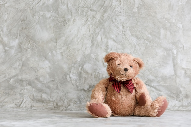 Cute puffy teddy bear toy sit alone in cement wall background