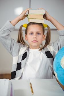 Cute pupil balancing books on head in a classroom