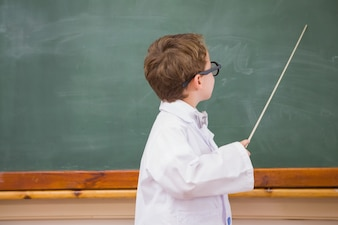 Cute pupil holding stick and pointing blackboard