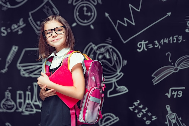 バックパックを持って学校に行き、学校に戻って手で予約する準備をしている眼鏡のかわいい生徒