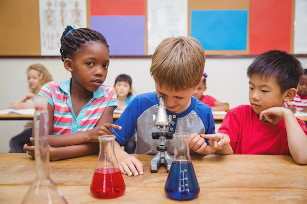 귀여운 학생 현미경을 통해 찾고