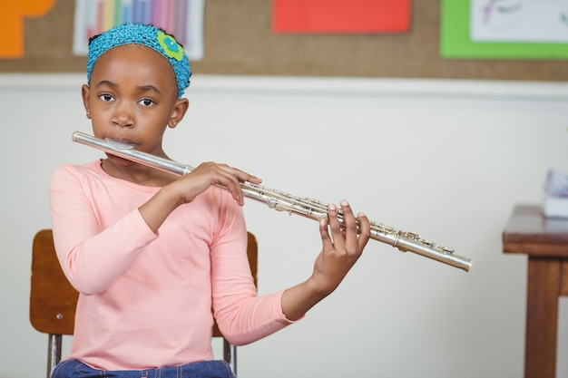 Cute pupil playing flute in a classroom