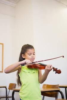 小学校の教室でかわいい瞳孔バイオリンを弾く