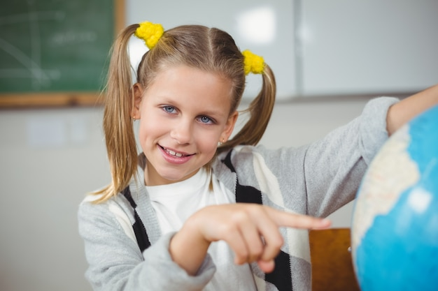 Cute pupil pointing on globe in a classroom